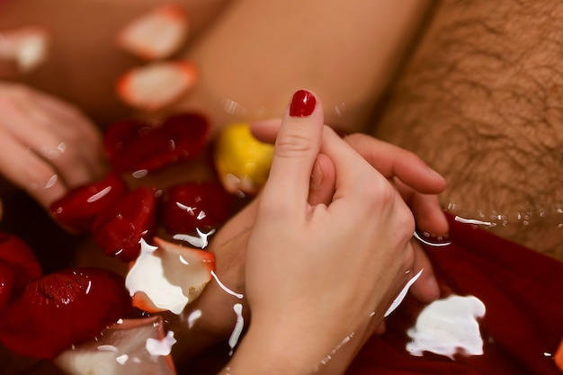 Man and woman holding hands in the bathtub close-up Free Photo