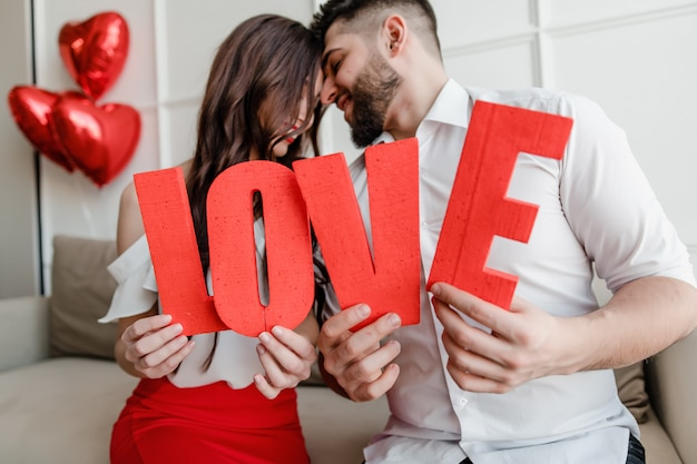Man and woman holding red love letters with heart shaped balloons at home sitting on couch Premium Photo