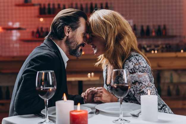 Man and woman leaned against each other holding hands in a restaurant Premium Photo
