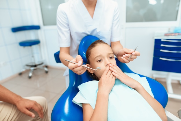 A man and a woman led the girl to see a dentist Premium Photo