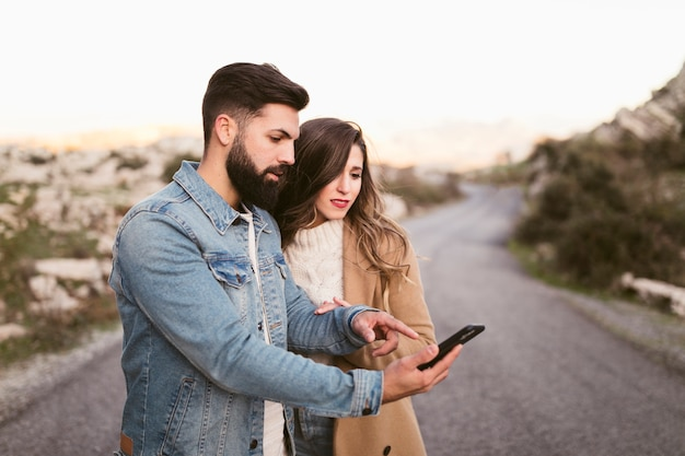 Man and woman looking on phone on road Free Photo