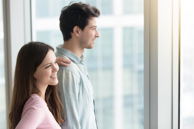 Man and woman looking through window at city scenery Free Photo