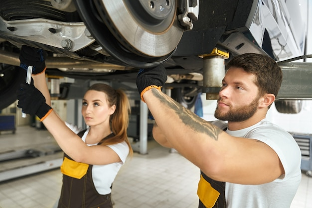 Man and woman mechanics repairing car undercarriage. Free Photo