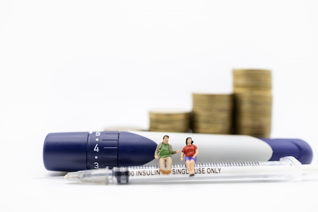 Man and woman miniature figure sitting on insulin syringe with lancet with stack of gold coins. Premium Photo