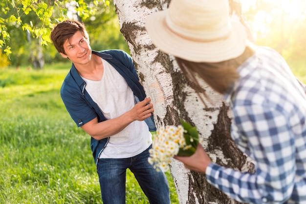 Man and woman playing around thick birch Free Photo