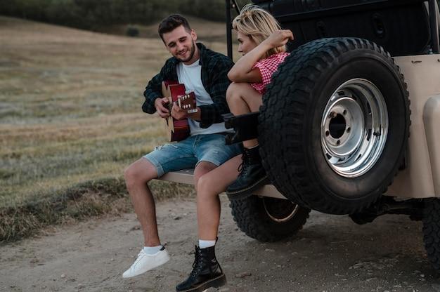 Uomo e donna che suonano la chitarra mentre viaggiano in auto = Foto Gratuite