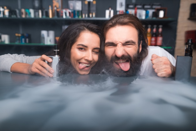 Man and woman posing on camera with electronic cigarette. Premium Photo