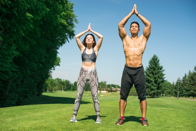 Man and woman practicing yoga outdoor Free Photo