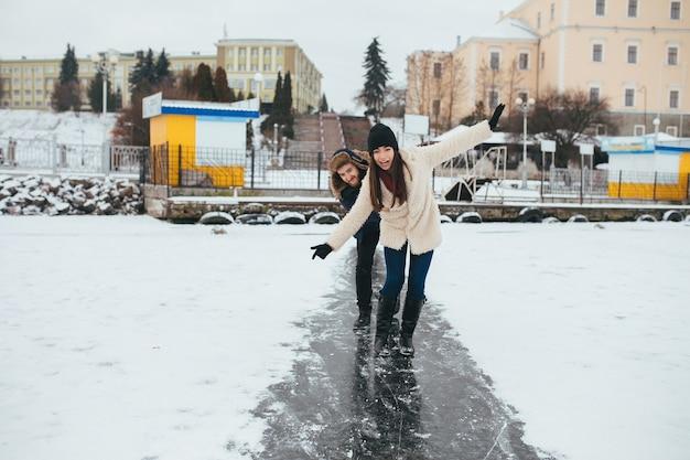 Uomo e donna che cavalcano sul ghiaccio su un lago ghiacciato Foto Gratuite