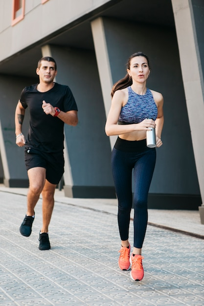 Man and woman running in urban environment Free Photo