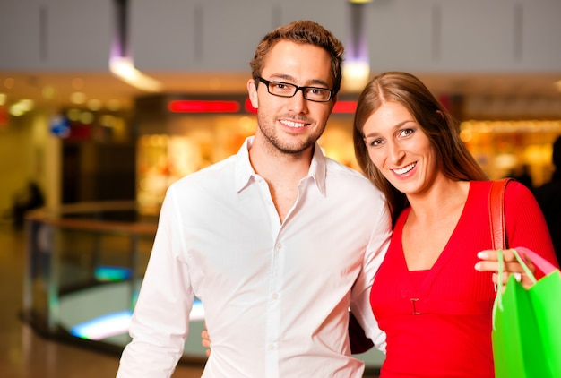 Man and woman in shopping mall with bags Premium Photo