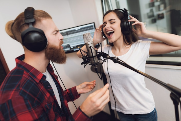 Man and a woman sing a song in a modern recording studio. Premium Photo