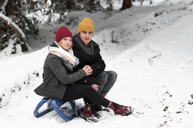 Man and woman sitting on the sleigh Free Photo