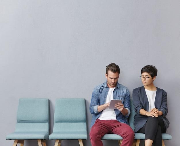 Uomo e donna che si siedono nella sala d'attesa Foto Gratuite