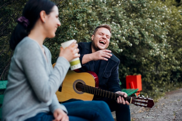 Man and woman spending time together with guitar outdoors Free Photo