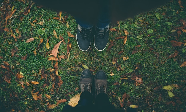 Man and woman stand opposite each other. close up of feet in winter boots in the autumn lawn Premium Photo