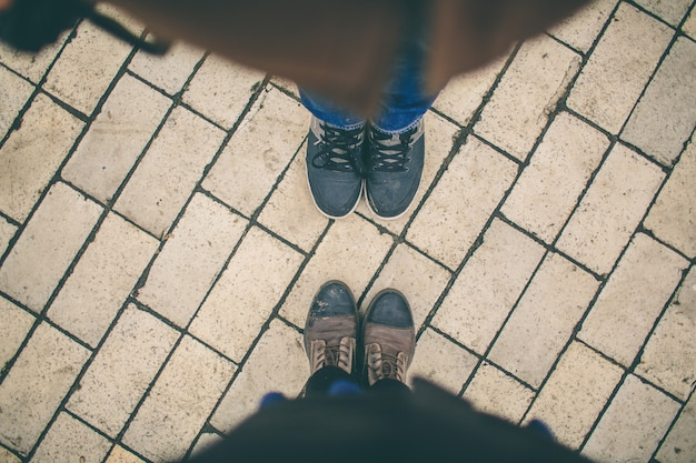Man and woman stand opposite each other. close up of feet in winter boots in the street Premium Photo