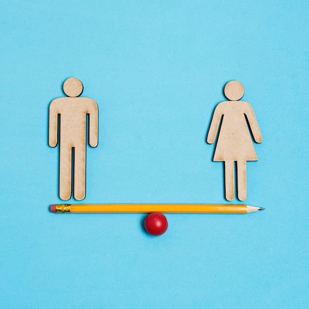 Man and woman standing on seesaw in balance Free Photo