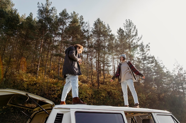Man and woman standing on a van outdoors Free Photo