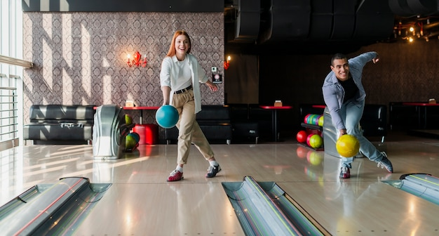 Man and woman throwing bowling balls on the alley Free Photo