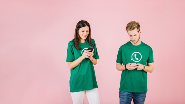 Man and woman using mobile phone on pink background Free Photo
