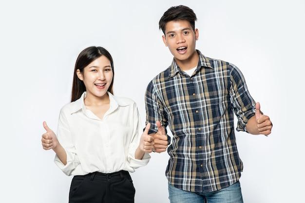 Uomo e donna che indossano camicie e fanno segni con le mani alzano i pollici Foto Gratuite