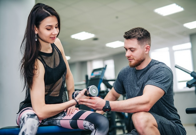 Man and woman with dumbbells flexing muscles in gym Premium Photo