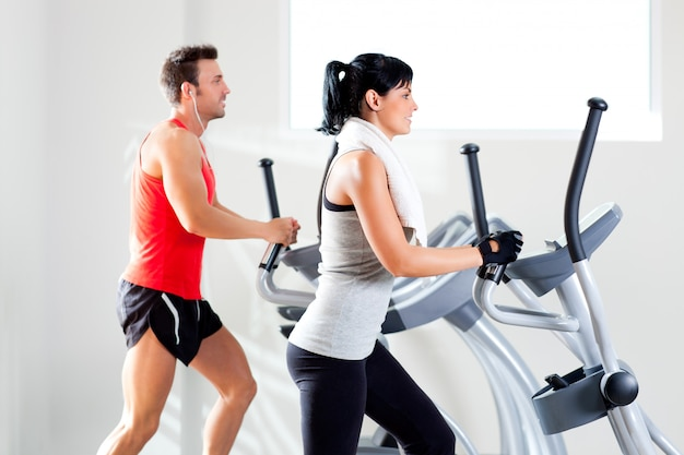 Man and woman with elliptical cross trainer at gym Premium Photo