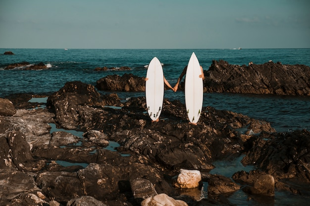 Man and woman with surf boards holding hands on stone coast Free Photo