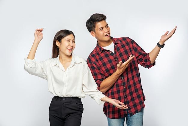 L'uomo e la donna indossavano camicie e allungavano felicemente le mani di lato Foto Gratuite
