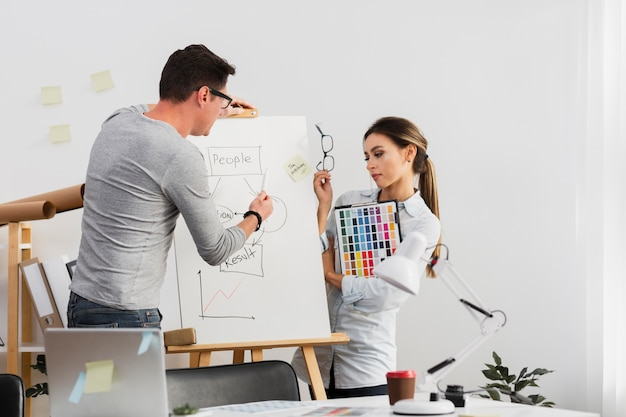 Man and woman working on a diagram Free Photo