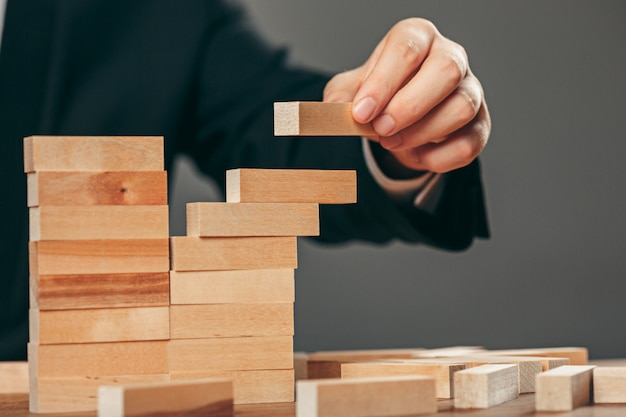 Man and wooden cubes on table. management concept Free Photo