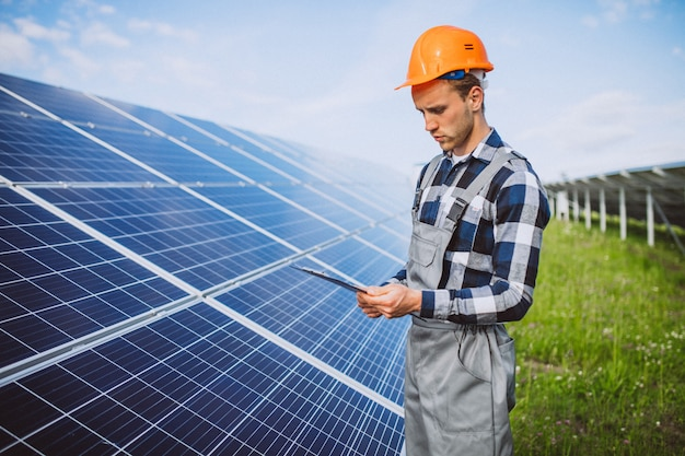 Man worker in the firld by the solar panels Free Photo