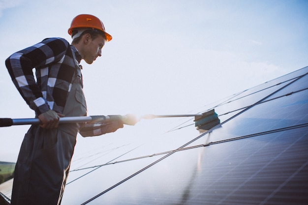 Man worker in the field by the solar panels