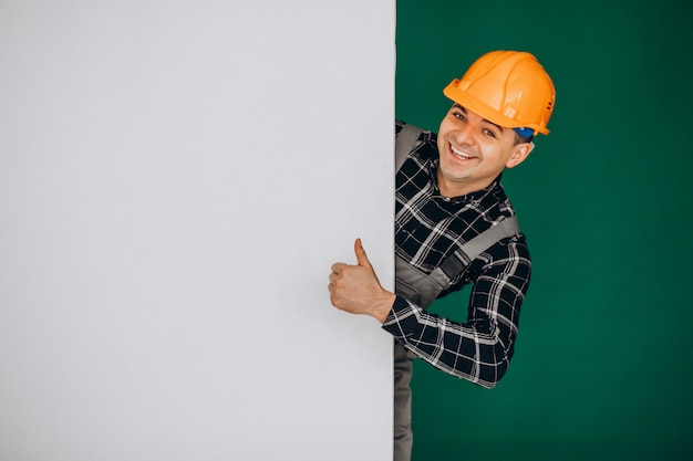 Man worker in hard hat isolated on green wall Free Photo