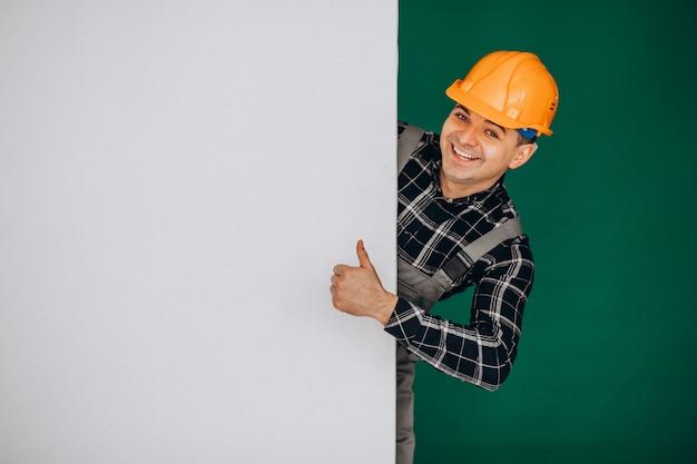 녹색 벽에 고립 된 모자에 남자 노동자 무료 사진
