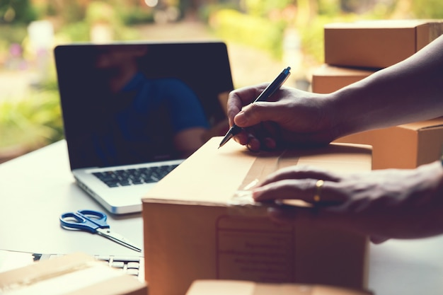 Man worker writing customer address deliver shipment online sales.  small business owner.shipment online sales Premium Photo