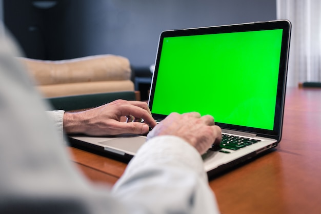 녹색 화면 컴퓨터에서 집에서 일하는 사람. 프리미엄 사진