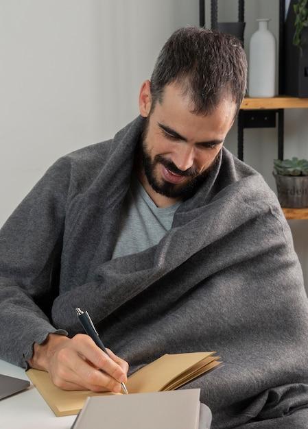 Человек работает из дома и пишет в записной книжке Бесплатные Фотографии