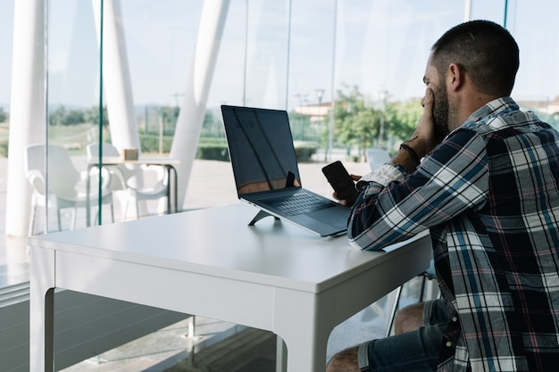 Man working in front of the laptop and with a mobile in his hand in a workspace Free Photo