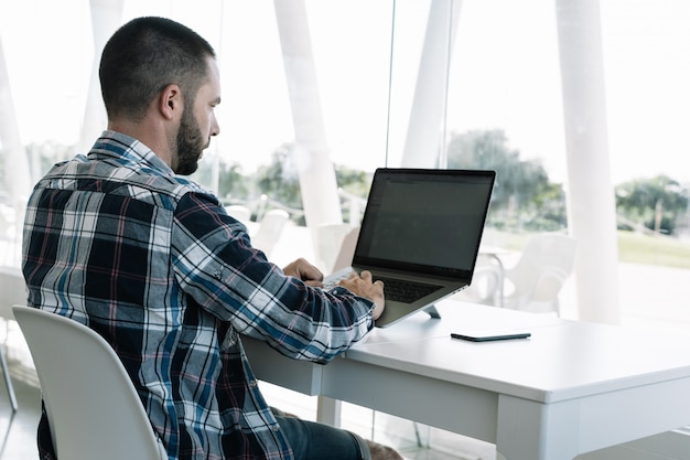 Man working in front of the laptop in a workspace Free Photo