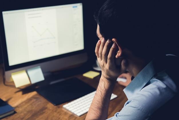 Man working on his desktop pc at night doing overtime work Premium Photo