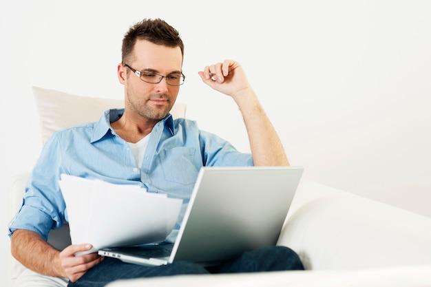 Uomo che lavora a casa con il laptop Foto Gratuite