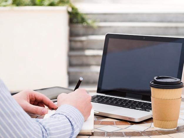Equipaggi lavorare al computer portatile fuori mentre mangiano il caffè Foto Gratuite