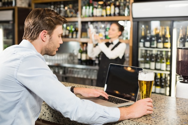 Man working on laptop with beer in hand Premium Photo