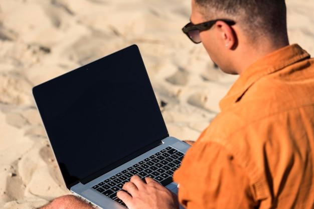 Человек, работающий на ноутбуке на пляже Бесплатные Фотографии