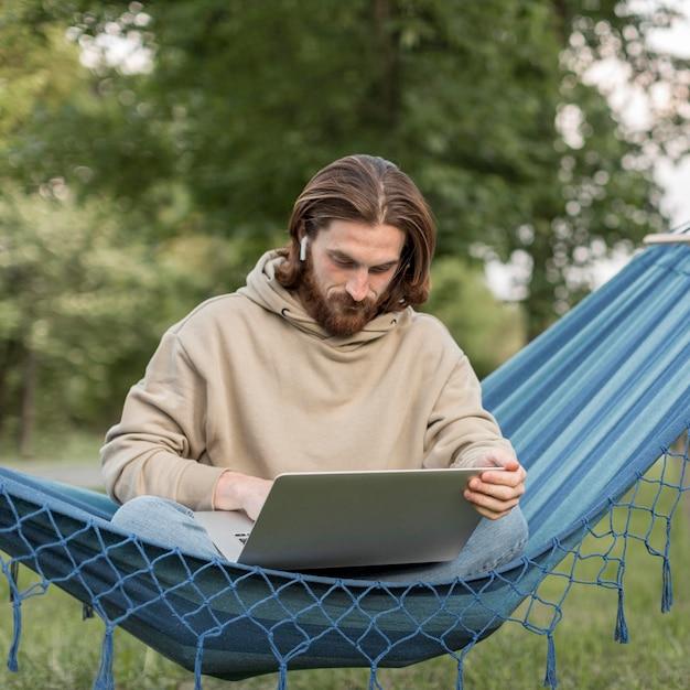 Человек работает на ноутбуке в гамаке Бесплатные Фотографии