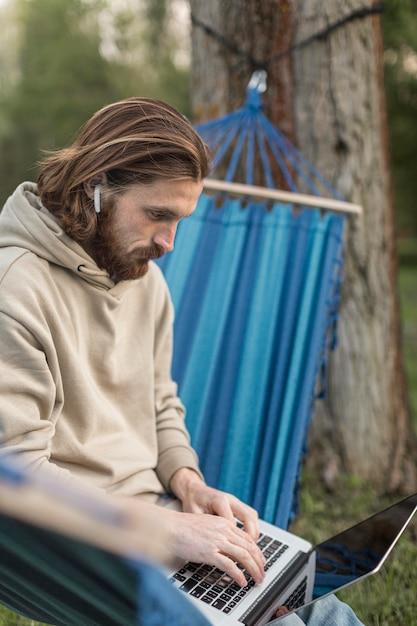 ハンモックに座っている間ノートパソコンで作業する人 無料写真