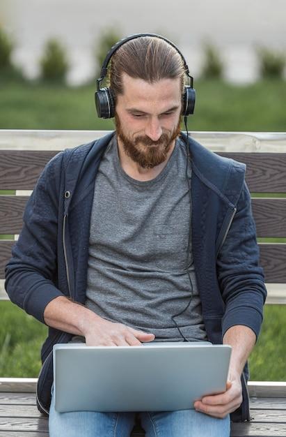 Человек работает на ноутбуке с наушниками на открытом воздухе Бесплатные Фотографии