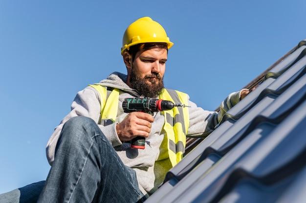 지붕 전면보기에서 작업하는 남자 무료 사진
